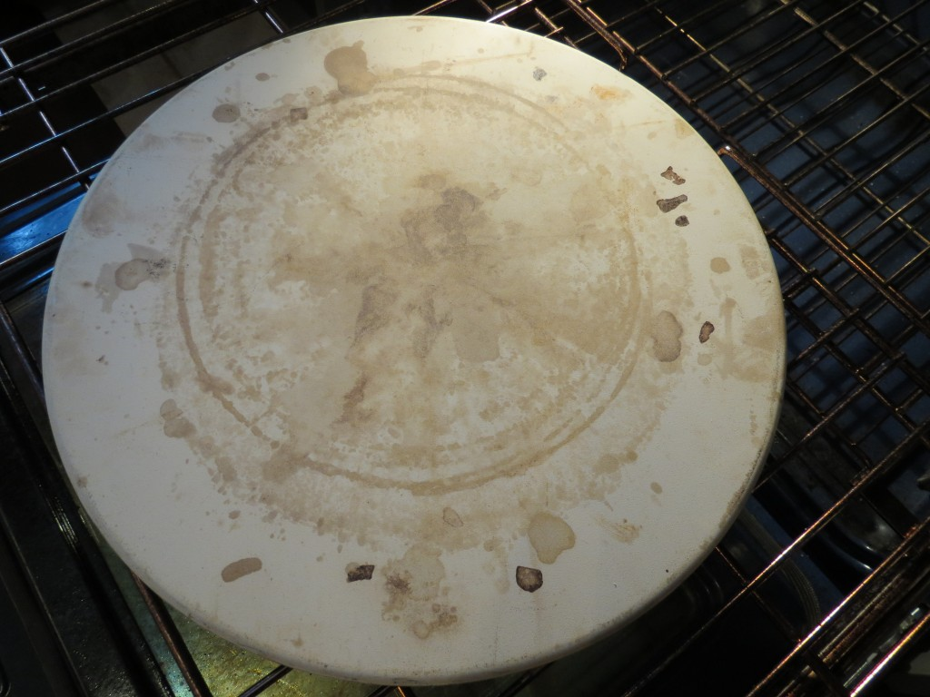 My old pizza stone.  Stained  from years of use, but still does the job!  I insert it in the oven before I start to preheat it, so that it's nice and hot when I put the pizza in to bake.  Makes for a nice crust.